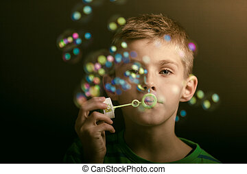 Young boy blowing iridescent bubbles - Young boy blowing...