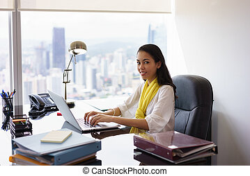 Business Woman Assistant Typing On PC And Smiling At Camera
