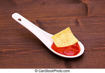 Teaspoon with hot sauce on wooden table