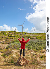 Windpower - A young boy standing infront of coastal...