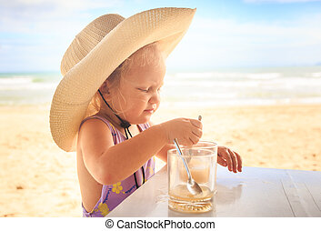 Little Blond Girl in Large Hat Drinks Juice with Spoon -...