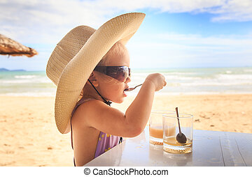Blond Girl in Large Hat Sunglasses Drinks Juice with Spoon -...