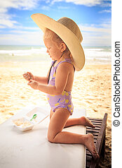 Blond Girl in Large Hat Stands on Knees with Spoon on Table...