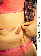 Woman measuring her waistline - Weight loss, healthy...