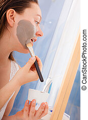 Woman applying mud mask on face in bathroom