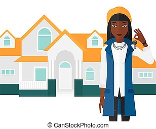 Real estate agent with key - An african-american woman...