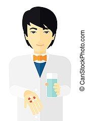 Pharmacist giving pills - An asian pharmacist holding in...