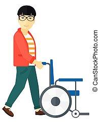 Man pushing wheelchair - An asian man pushing empty...