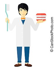 Dentist with dental jaw model and toothbrush. - An asian...
