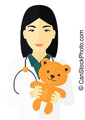 Pediatrician holding teddy bear - An asian pediatrician with...