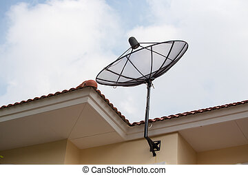home satellite dish over roof and sky background