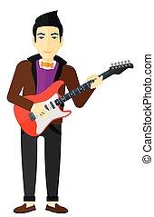 Musician playing electric guitar - An asian musician playing...