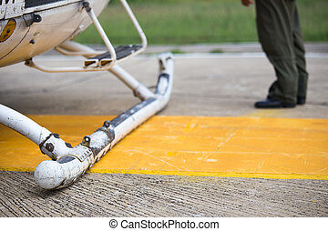 helicopter landing skids parking on helipad and pilot...