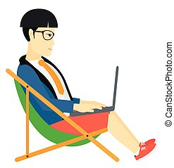Businessman sitting in chaise lounge with laptop - An asian...