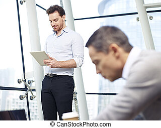 business people working in office - two caucasian business...
