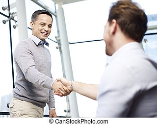 business executives shaking hands - two caucasian...