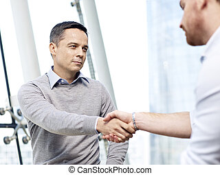 businessman shaking hands with competitor - caucasian...