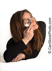 Young girl looking thru a loupe, isolated in white