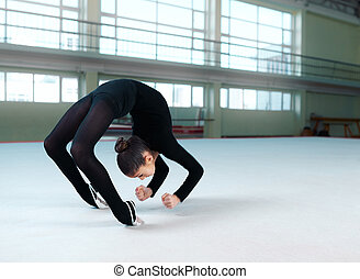 gymnast in black suit making a somersault on the floor