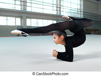 Little girl practicing gymnastic in gym-hall - Side view of...
