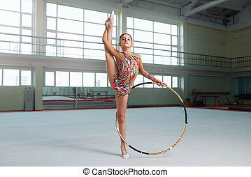 little gymnast in a nice suit doing stretching with hoop