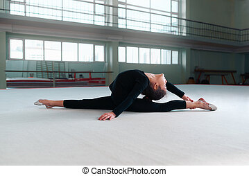 girl gymnast in a sweatsuit doing stretching exercises