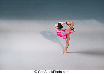 girl in pink gymnastic dress doing exercise - Side view of...