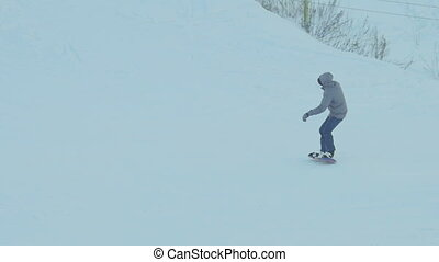 Snowboarding in the winter park - Snowboarder accelerates...