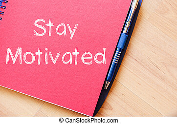 Stay motivated write on notebook - Stay motivated text...