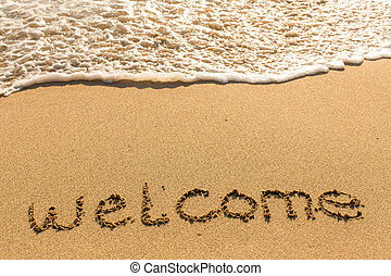 Welcome - inscription on sand beach with the soft wave