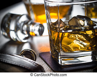 Whiskey on the rocks on a wooden table - One glass of...