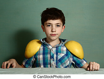preteen cute boy play with grape fruit halfs as he is a...
