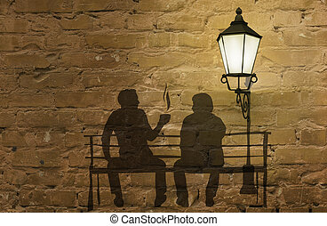 Two silhouettes on a bench - coffee story art on the wall...