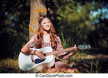 Beautiful young hippie girl sitting under the tree and...