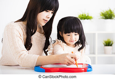 Mother or teacher helping child daughter to writing