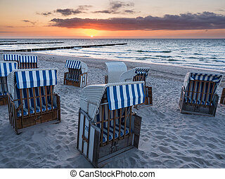 Beach chairs on the Baltic Sea coast with sunset