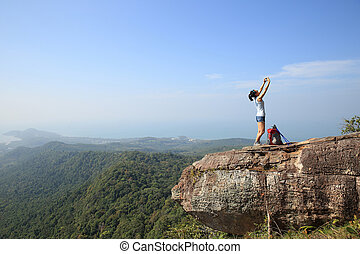 young woman backpacker taking photo with smartphone on...