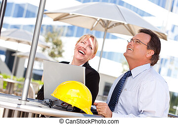 Businesswoman and Man Laughing While Working - Handsome...