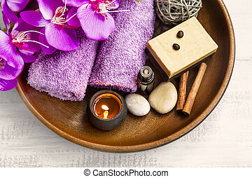 Spa products in wooden tray with towels,scent candle,orchid,...