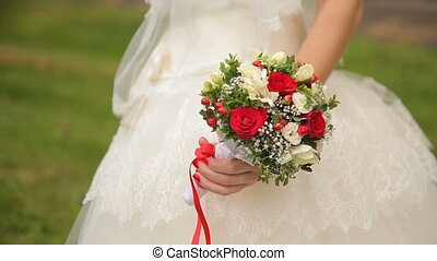 Bride holding a wedding bouquet made of roses, blackberries...