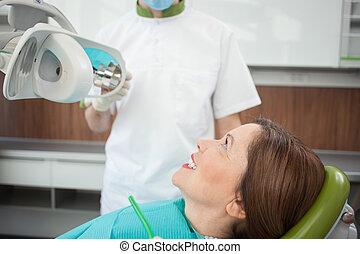 Cheerful mature lady is getting dental treatment