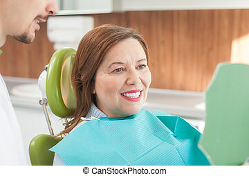 Cute old lady is visiting dental doctor