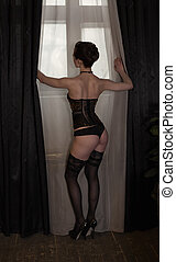 Woman in the corset near the window - Woman in lingerie...