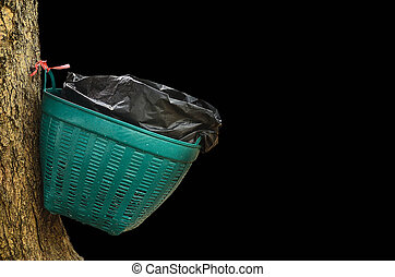 Waste basket on tree in black background