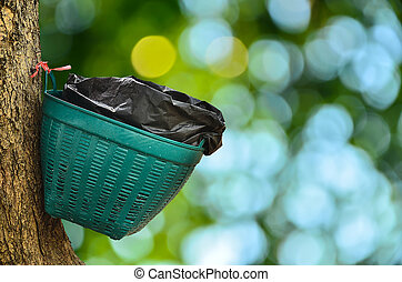 Waste basket on tree in sunny abstract  background