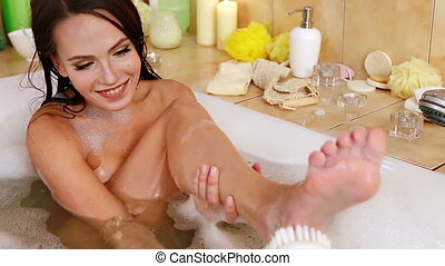 Woman taking foam bath and chiropody by brush in her...