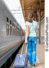 woman with a suitcase walking along the platform to the...