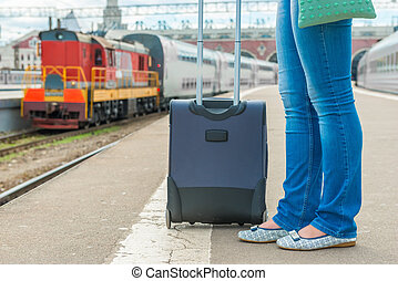 suitcase and female feet waiting for a train at the station