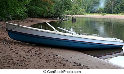 boat on the sandy shore of the rive - Empty rowboat on the...