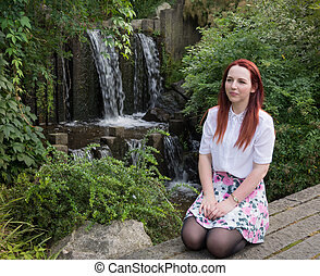 young woman in front of a waterfall III